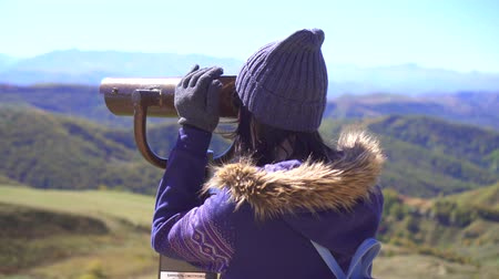 looking distance : Girl on the observation deck looks at the mountains through binoculars and then looks into the camera Stock Footage