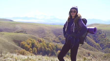horská pastvina : Portrait of woman tourist with backpack, mountains in the background,slow mo Dostupné videozáznamy