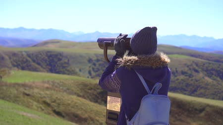 looking distance : Tourist girl on the observation deck looks at the mountains through binoculars,slow mo Stock Footage