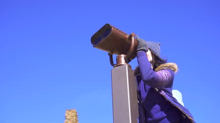 looking distance : Girl on the viewing platform looks at the mountains through binoculars,slow mo Stock Footage