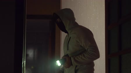 thieve : Masked burglar with flashlight in someone apartment Stock Footage