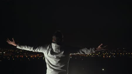 çığlık atan : male winner posture spread his arms against the background of the night city Stok Video