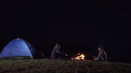 костра : Tourists sit near the tent and fry marshmallows on a fire in the mountains at night Стоковые видеозаписи