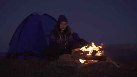 alkony : Woman camping at night sitting near the tent and basking by the fire,slow mo