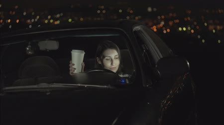 black cab : portrait young woman driver drinking coffee and using smartphone at night