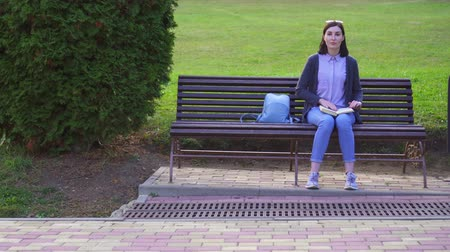 sentido : Girl with visual impairment in the Park reads a book with Braille with her fingers