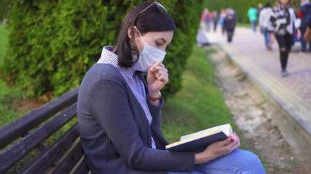 filtro aire : Girl sitting on a bench in a protective medical mask with a book in her hand and coughs