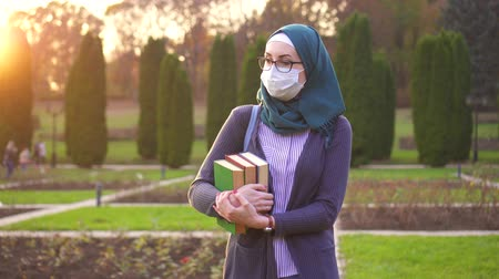 soluções : Muslim student with books in hijab with backpack and medical protective bandage on her face in the park