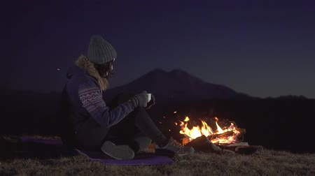 akşam vakti : Camping young woman sitting and drinking from a Cup around the fire at night in the mountains,slow mo