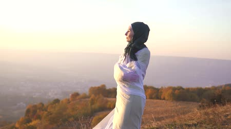 palestina : portrait of a stylish girl in a hijab at sunset in the mountains stands on the edge of a cliff