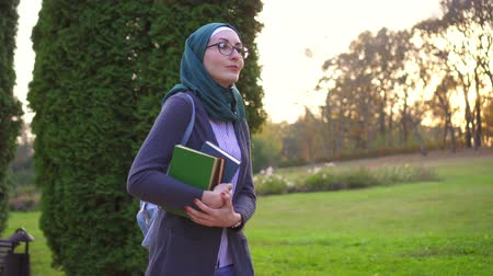 преподаватель : Student muslim woman in hijab with a books go in the park Стоковые видеозаписи