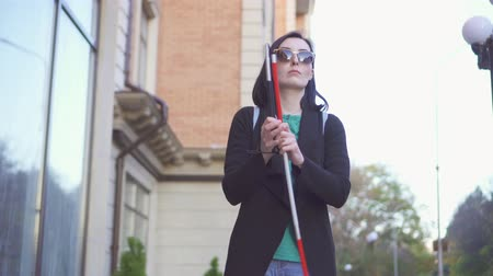 blindness : Young pretty woman in glasses with a cane walking down the street Stock Footage