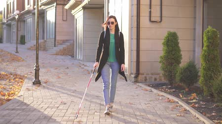 blindness : Young blind woman with a backpack with a cane goes through the city sunray,slow mo