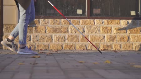 blindness : Woman walking down the street with a cane for the visually impaired,slow mo Stock Footage
