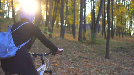malaya : Muslim woman in a hijab and with a backpack on her back rides a bicycle in autumn park Stok Video