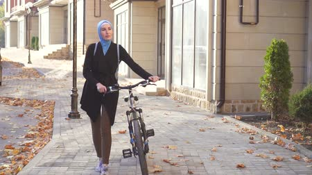 malajské : Muslim woman in hijab with a bicycle in the city,slow mo