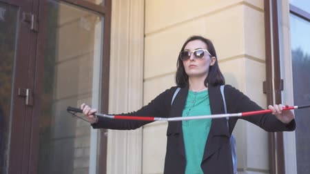 blindness : Blind pretty woman lays out a cane in the street,slow mo