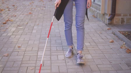 impaired : Young woman visually impaired with a cane walking around the city