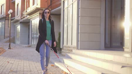 слепой : Young blind woman with a backpack with a cane goes through the city sunray