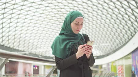 malaya : Pretty muslim woman in a hijab stands in a shopping center and uses the phone Stok Video