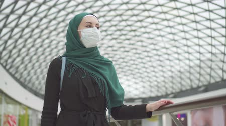 malaya : Portrait pretty muslim woman in a hijab with a backpack and a medical mask on her face goes shopping Stok Video