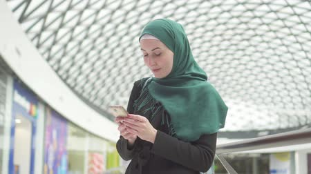 malaya : Young muslim woman in a hijab stands in a shopping center and uses the phone,slow mo Stok Video