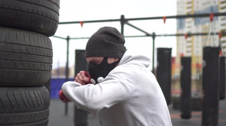 raiva : Man athlete in a training mask and boxing types boxing on the street training ground