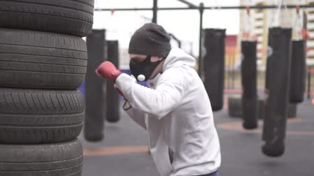fury : Man athlete in a training mask and boxing types boxing on the street training ground,slow mo
