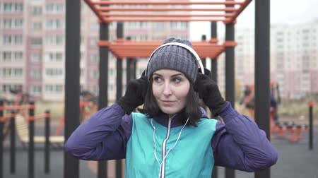 dinleme : Portrait woman athlete with headphones on the street playground,slow mo Stok Video