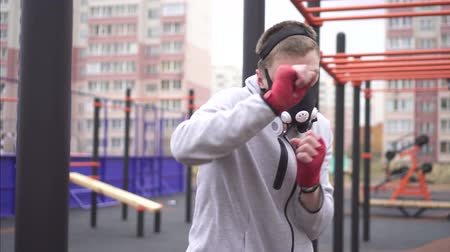 fury : Man in a training mask on his face boxing on a sports street playground