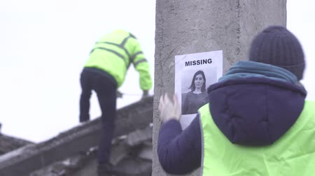 ilk yardım : volunteer sticks a poster about the loss of a person during a natural disaster