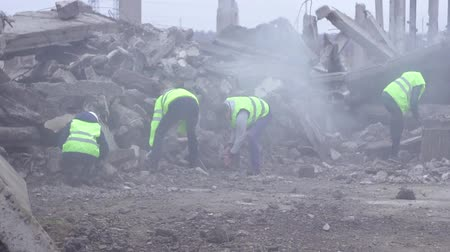 demolition : a group of rescue workers dismantle the rubble of the destroyed house Stock Footage