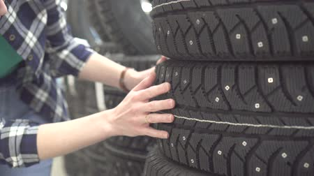 díszgomb : girl in a plaid shirt chooses winter tires for a car in a shop