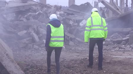 demolition : two employees of service of rescue the signal in the green vests on the ruins after the earthquake