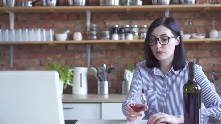 cheerless : lonely woman business woman drinks wine in the kitchen looking at a laptop Stock Footage