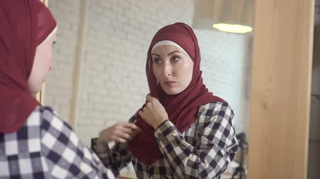 szerény : Muslim woman wearing a scarf in front of a mirror