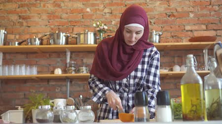 arabština : Young muslim woman in kitchen cuts vegetables to cook food