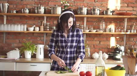 omeleta : Woman in a shirt and headphones listening to music dancing in the kitchen and cutting vegetables