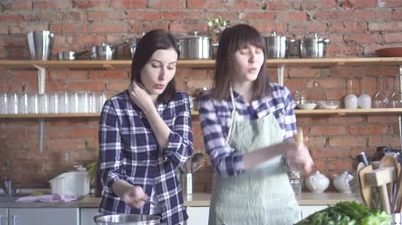 lesbian couple : cute girls dancing and singing in the kitchen while cooking Stock Footage