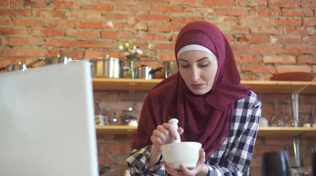 časopis : Young muslim woman in the kitchen looking at the laptop training video cooking dinner