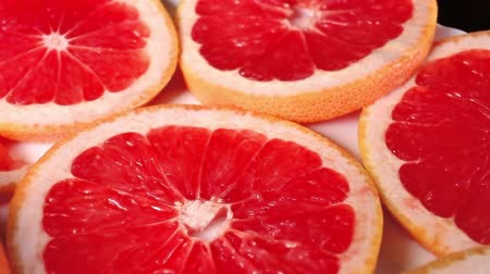 grejpfrut : Grapefruits. Grapefruit slices rotating pattern macro texture background backdrop footage video.