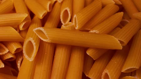 Whole grain pasta penne rotating pattern macro texture background backdrop footage video.