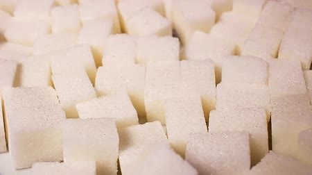 White sugar cubes. Lump sugar cube rotating pattern macro texture background backdrop footage video. Стоковые видеозаписи