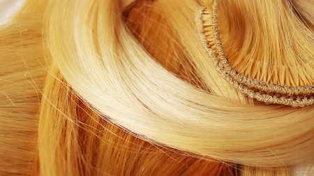 Hair extension cutted hair fibers blonde weft rotating pattern macro texture background backdrop footage video.