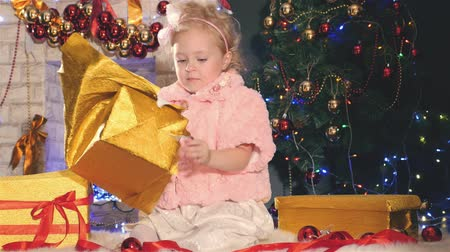 christmas dekorasyon : Cute little girl unpacking gift box, near decorated Christmas tree Stok Video