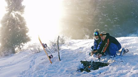 Snowboarders couple warm up by the campfire outdoor at mountain