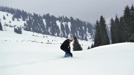 Snowboarder young man riding at snowy alps mountains, Swiss
