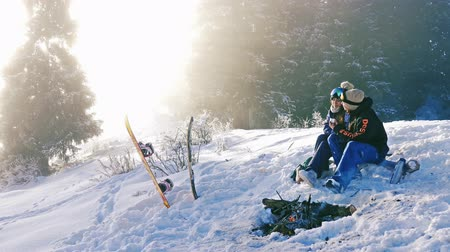 Timelapse of snowboarders couple warm up by campfire outdoor, mountain Stock Footage