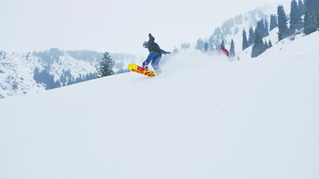 Footage of snowboarder and skier men fast riding at mountains Stock Footage