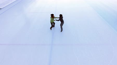 Aerial view of ice skating two women friends outdoor, ice rink Medeo Stock Footage